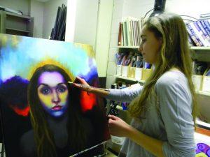 Senior Elle Stang finalizes her self portrait in Advanced Art Studio class. Photo: John Morrison