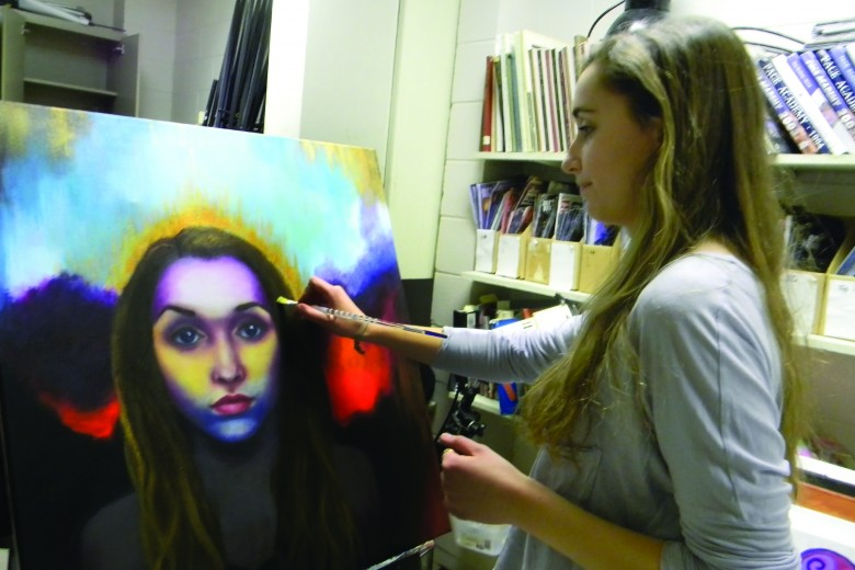 Senior Elle Stang finalizes her self portrait in Advanced Art Studio class. Photo: John Morrison