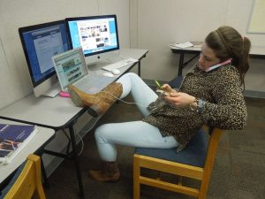 Junior Elizabeth Willis sits, entranced by her various tech devices. Photo: Julia Beck