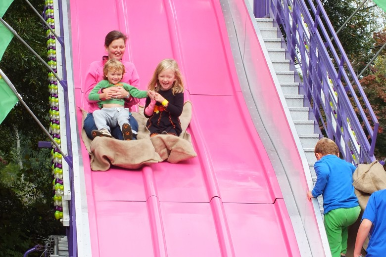 A mother and her children enjoy a slide at the Pace Fall Fair.