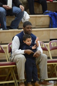 Head Coach Demetrius Smith steals a quiet moment with son Noah before the start of the Elite Eight game against Vidalia. Photo: Fred Assaf
