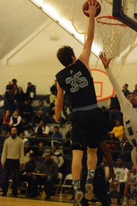 Junior Zack Kaminsky goes up for a slam dunk against KIPP guard Eric Conway. Photo by Fred Assaf.
