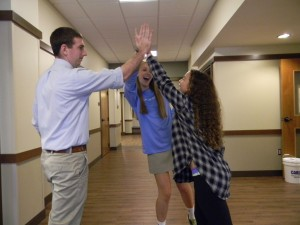 Students Mary Brooks Perkey and Zoe Weitzner excitedly high-five Mr. Sandoe as they discuss their trip to Vietnam.