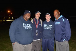 Coach Clemont Rouviere (second from left) gathers with fellow Pace football coaches at the bonfire on Dec. 3.