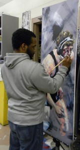 Donice Bloodworth works on a painting of a wrestle athlete for the Art Faculty Show opening February 17. Photo: Alyse Greenbaum