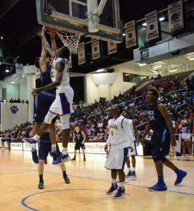 Sophomore Isaiah Kelly (blue) throws down a dunk over William Jarrell of Crawford County in the GHSA Final Four. Kelly had 20 points on the night. Photo: Fred Assaf