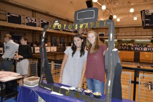 Seniors Lizabeth Frohwein and Laura Shelton attract students to their club.