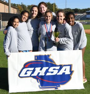 The girls cross country team revels in their 3rd place finish at State. Photo: Fred Assaf