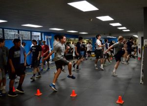 Athletes perform a variety of movement exercises to activate the nervous system and warm up the muscles before strength training. Photo: Marc Mitchell